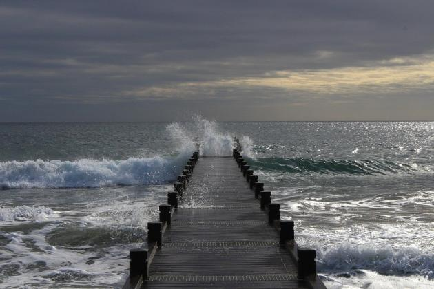 Sea waves break on wooden sea pier