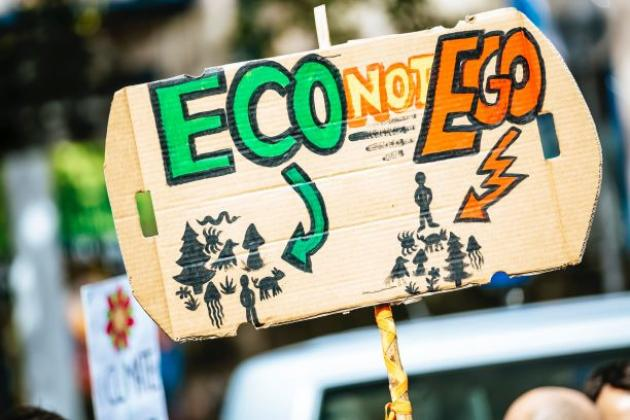 Person holding eco-not-ego sign